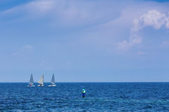 Three sailing centerboarder in open blue sea Royalty Free Stock Images