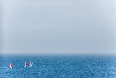 Three sailingboats at a regatta Stock Photos