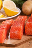 Three salmon pieces on a chopping board. Three fresh salmon pieces with lemons on a chopping board Stock Image