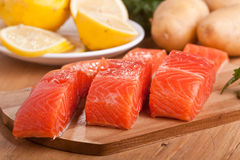 Three salmon pieces on a chopping board Stock Photography
