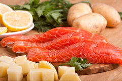 Three salmon pieces on a chopping board. Three fresh salmon pieces with vegetables on a chopping board Royalty Free Stock Photo
