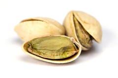 Three salt pistachio nuts isolated on white backround close up. Macro Royalty Free Stock Photos