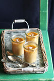 Three salted caramel pots de creme on a rustic tray. Three salted caramel pots de creme Royalty Free Stock Images