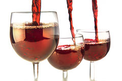 Three at same time. Closeup photo of three glasses beeing poured with red wine at same time Royalty Free Stock Images