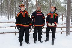Three Sami men in snow in Lapland, Finland. LAPLAND, FINLAND – FEBRUARY 2, 2017: Three Sami men in Finnish Lapland wear colorful woolen clothing in the snow Royalty Free Stock Photos