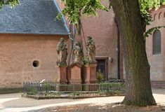 Three sandstone sculptures in front of the church of st. marcellinus and peter, seligenstadt, hesse, germany.  stock photo
