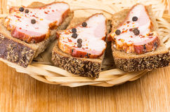 Three sandwiches with bacon and peppers in wicker basket Stock Photo