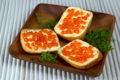 Three sandwiches with red caviar on wooden plate Royalty Free Stock Images