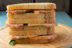 Three sandwiches with smoked pork on wooden plate Stock Photos
