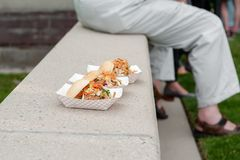Three sandwiches in to-go cartons on a concrete ledge royalty free stock photo