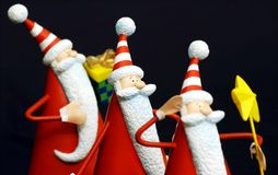 Three santa claus. Ready for christmas in a black background stock photo