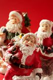 Three Santa Claus figurines over red background Stock Image