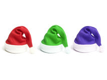 Three santa claus hats. In red, green and blue colors over white background Stock Images