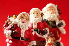 Three Santa Claus over red background, studio Royalty Free Stock Photos