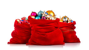 Three Santa Claus red bags with Christmas toys on white. Background Royalty Free Stock Photo