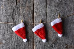 Three Santa hats hanging from a piece of twine. Stretched across a rustic wood wall Royalty Free Stock Photography