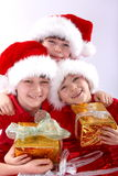 Three santa kids with gifts royalty free stock images