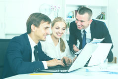 Three satisfied coworkers different sexes working in company off Stock Photo