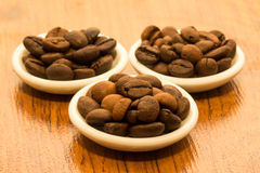 Three saucers with fragrant coffee beans Stock Images