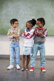 Three school kids talking to each other in classroom. At school royalty free stock photography