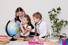 Three schoolgirls girls learn world geography lesson on the map stock images