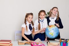 Three schoolgirls girls learn world geography lesson on the map stock photos