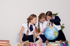 Three schoolgirls girls learn world geography lesson on the map stock image