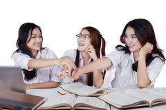 Three schoolgirls pile up their hands Royalty Free Stock Photography