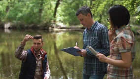 Three scientists exploring water in lake. Three ecologists wearing casual clothing exploring lake and taking water sample Stock Photography