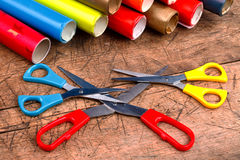 Three scissors with wrapping paper rolls Stock Images