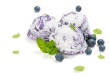 Three scoops of blueberry ice cream. Dessert of blueberry ice cream fresh berries with leaves of mint on white background, selective focus royalty free stock photography