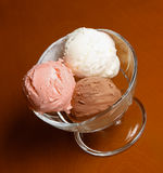 Three scoops of chocolate, strawberry and vanilla ice cream in g Royalty Free Stock Photo