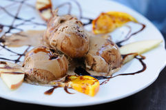 Three scoups of coffee ice-cream. With chocolate sirup and slices of orange on white plate Royalty Free Stock Photo