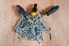 Three screwdrivers on a pile of screws Royalty Free Stock Photos