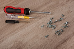 Three screwdrivers and screws lay on wooden table Stock Photography