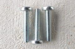 Three screws on a white wooden table Stock Photo