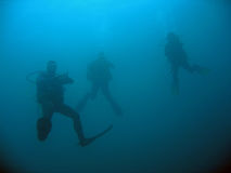 Three scuba divers on deep dive. Scuba divers acsending from a deep wreck dive in the philippines stock photos