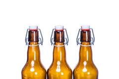Three sealed beer bottles staying in row Royalty Free Stock Photos