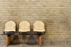Three seated bench against yellow brick wall Royalty Free Stock Image