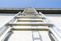 Aluminum ladder. Three section aluminum ladder leaning against house stock image