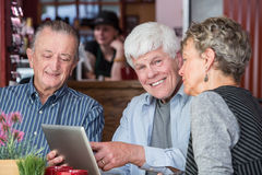 Three senior citizens using tablet computer in bistro Stock Photography
