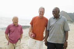 Three senior men walking on beach Stock Photos