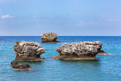 Three separate rocks offshore in sea Stock Images
