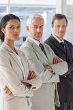 Three serious business people standing together Stock Image