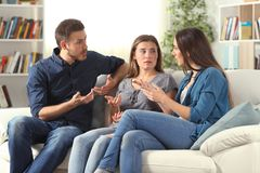 Three serious friends talking sitting on a couch at home stock image
