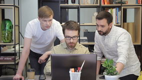 Three serious programmers brainstorm before the laptop. stock footage