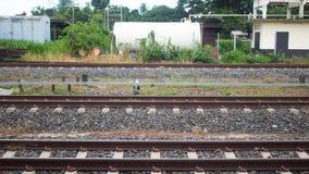 Three sets of railroad tracks run straight Stock Photo