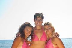 Three girls in bikinis royalty free stock images