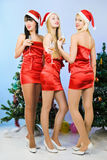 Three girls wearing santa claus clothes Royalty Free Stock Photos