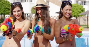 Three playful women with water pistols stock footage
